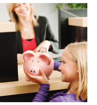 Photo of young girl at a teller line in a bank handing her piggy bank to a teller