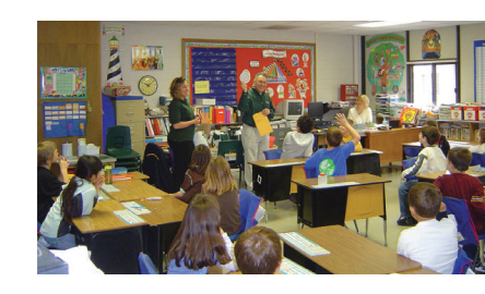 Photo of two bank employees teaching a number of second grade students in a classroom about saving